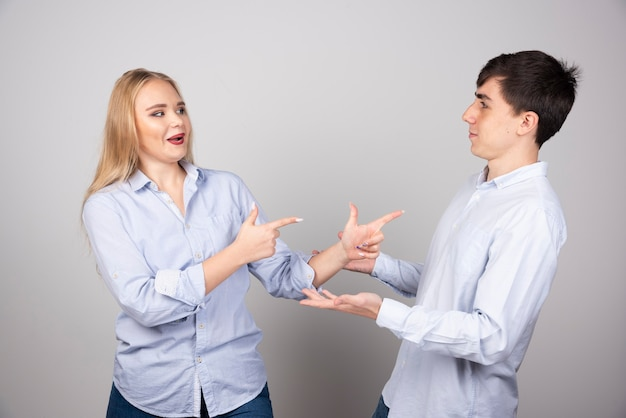Portret młodej pary wskazując palcami stojąc na szarej ścianie.