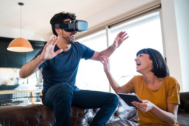 Portret młodej pary wspólnej zabawy i grania w gry wideo w okularach vr podczas pobytu w domu