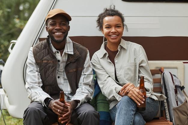 Portret młodej pary z afryki, która relaksuje się na świeżym powietrzu podczas biwakowania z przyczepą kempingową i spogląda...