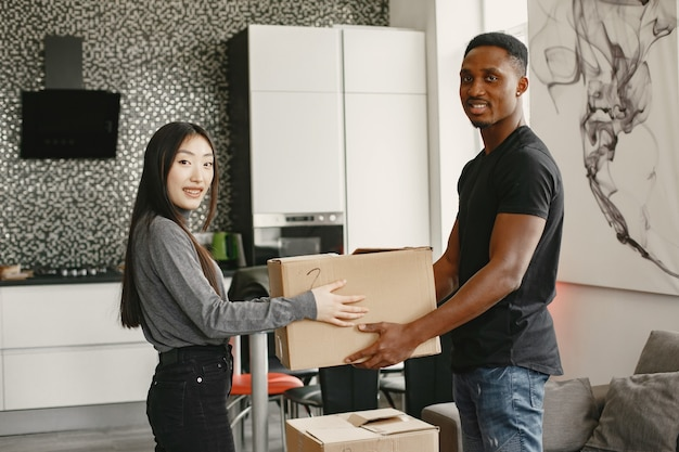 Portret młodej pary z kartonów w nowym domu, koncepcja przeprowadzki.