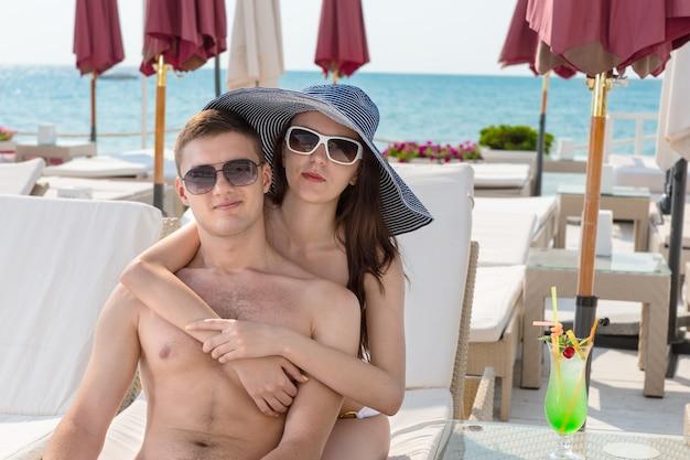 Portret młodej pary z ramionami wokół siebie siedzących razem na leżaku z tropikalnym napojem na słonecznym pokładzie nad oceanem luxury beach resort