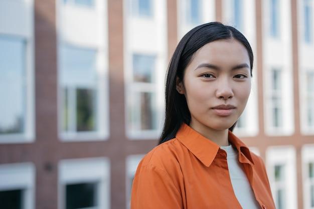 Portret młodej pewnej siebie kobiety biznesu na ulicy zamyślony azjatycki student patrząc na kamerę