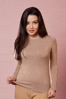 Portret młodej pięknej azjatyckiej brunetki w jasnobrązowym swetrze.