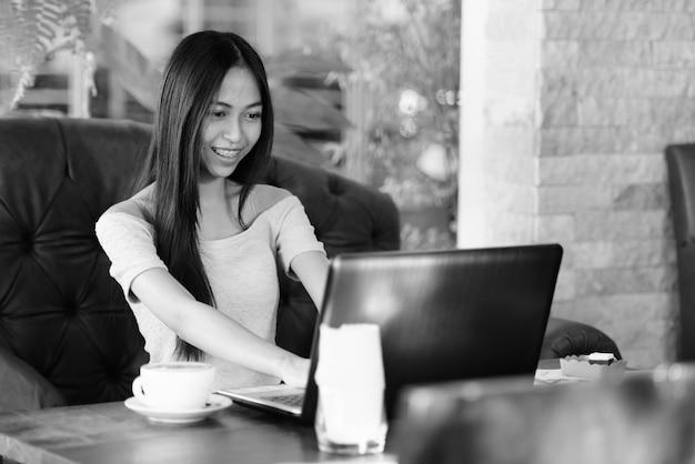 Portret młodej pięknej azjatyckiej dziewczyny relaksującej się w kawiarni na świeżym powietrzu w czerni i bieli