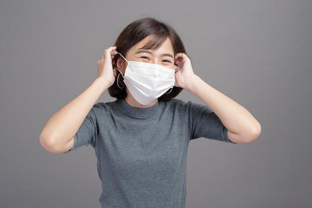 Portret młodej pięknej azjatyckiej kobiety noszącej maskę chirurgiczną na szaro