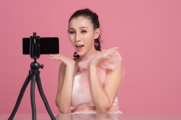 Portret młodej pięknej azjatyckiej kobiety profesjonalny vlogger kosmetyczny lub bloger nagrywający do udostępnienia w mediach społecznościowych przez smartfona na statywie.