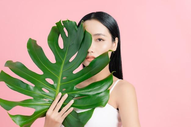 Portret młodej pięknej azjatyckiej kobiety trzymającej tropikalny liść na różowo