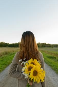 Portret młodej pięknej azjatyckiej kobiety w dziedzinie kwitnących słoneczników na zewnątrz