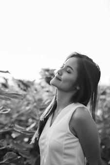 Portret młodej pięknej azjatyckiej kobiety w dziedzinie pięknych kwitnących słoneczników w czerni i bieli