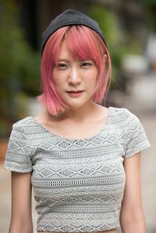 Portret młodej pięknej azjatyckiej kobiety z różowymi włosami na ulicach na zewnątrz