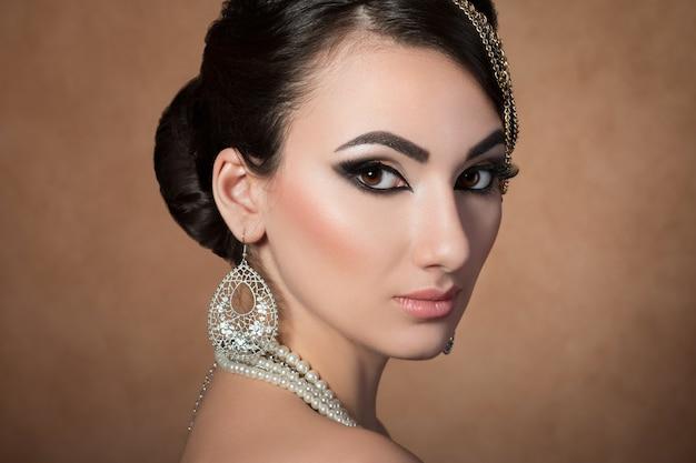 Portret młodej pięknej azjatyckiej kobiety z wieczorowym makijażem na beżu