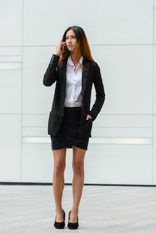 Portret młodej pięknej bizneswoman azjatyckiego na ulicach miasta na zewnątrz