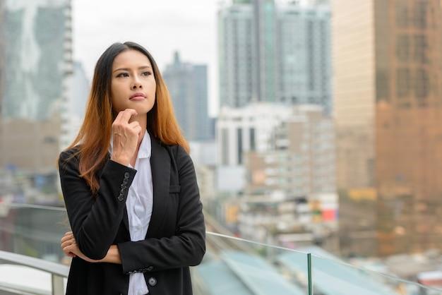 Portret młodej pięknej bizneswoman azjatyckiego z widokiem na miasto