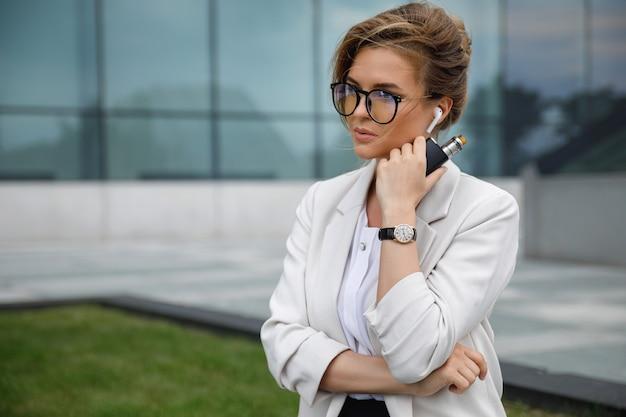 Portret młodej pięknej bizneswoman palenia vape