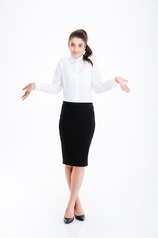Portret młodej pięknej bizneswoman wzruszając ramionami nad białą ścianą