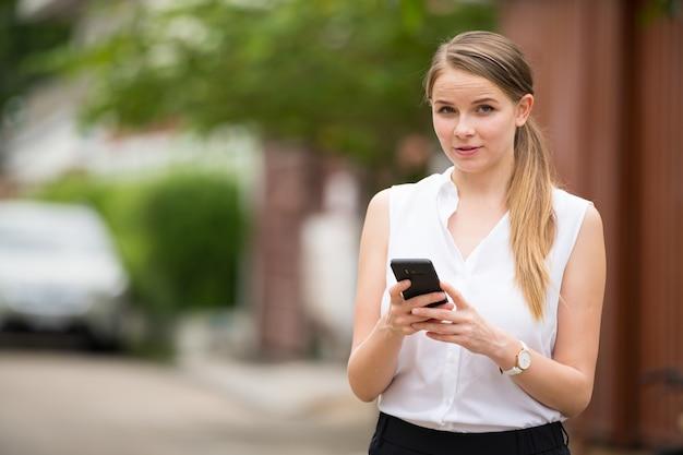 Portret młodej pięknej blond bizneswoman na ulicy na zewnątrz
