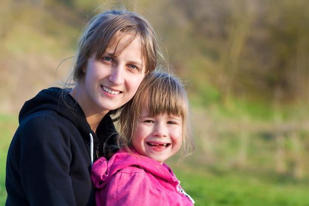 Portret młodej pięknej blond dziewczyny tulenie czule i opiekuńczo jej małej przedszkolnej bezzębnej siostry, obie uśmiechnięte radośnie w aparacie na zewnątrz. szczęśliwe relacje rodzinne i pojęcie przyjaźni.