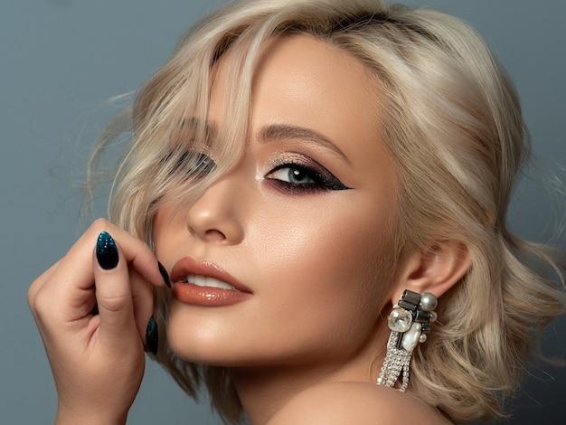 Portret młodej pięknej blond kobiety z wieczorem makijaż dotyka jej głowy. nowoczesne modne skrzydło eyelinera i piękny kolczyk.