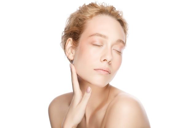 Portret młodej pięknej blond kobiety z zamkniętymi oczami, dotykając jej idealnie czystej skóry