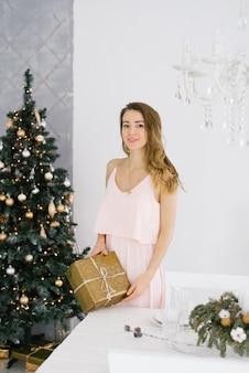 Portret młodej pięknej blondynki w różowej sukience z prezentem w dłoniach z salonem urządzonym na boże narodzenie.