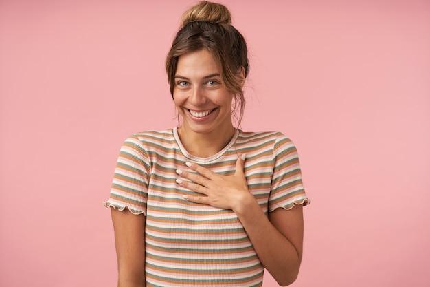 Portret młodej pięknej brązowowłosej kobiety z naturalnym makijażem, patrząc radośnie na aparat z szerokim uśmiechem, pozując na różowym tle w codziennym stroju