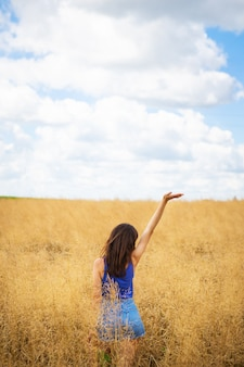 Portret młodej pięknej brunetki w niebieskiej koszulce i dżinsowych szortach stoi na środku pola, wystawiając twarz na słońce