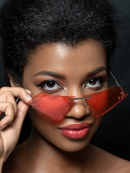 Portret młodej pięknej czarnej kobiety, patrząc na nowoczesne mody czerwone okulary przeciwsłoneczne
