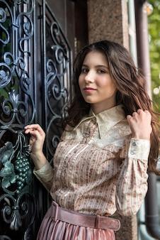 Portret młodej pięknej damy nosi modną tkaninę pozującą w pobliżu starych teksturowanych drzwi
