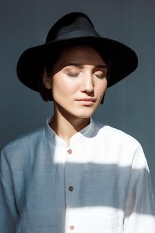 Portret młodej pięknej dziewczyny brunetka w czarnym kapeluszu.