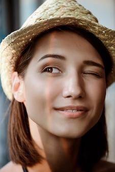 Portret młodej pięknej dziewczyny brunetka w kapeluszu, uśmiechając się, mrugając.