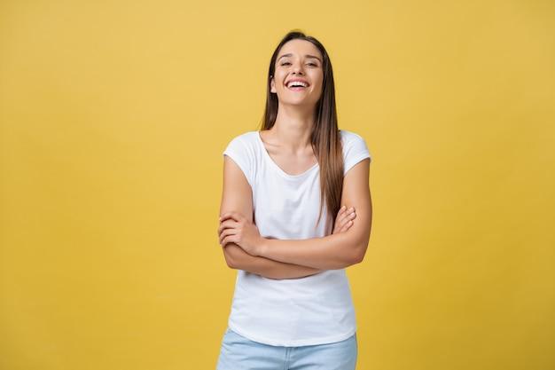 Portret młodej pięknej dziewczyny kaukaski z białą koszulę śmiejąc się na żółtym tle.