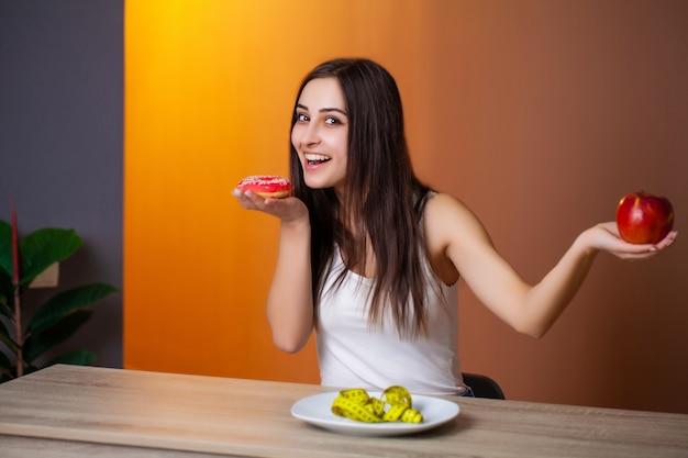 Portret młodej pięknej dziewczyny, która dokonuje wyboru między zdrowym jedzeniem a szkodliwym