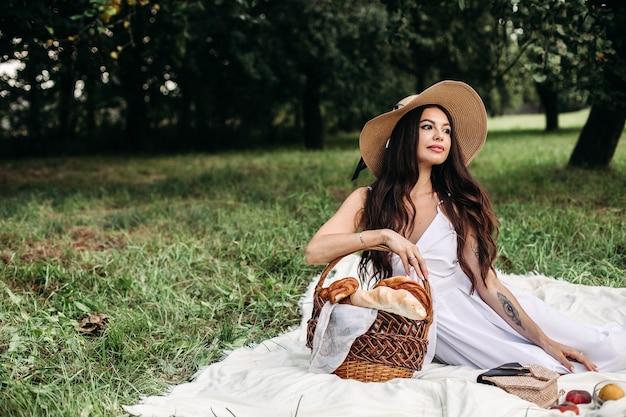 Portret młodej, pięknej dziewczyny o równych białych zębach, pięknym uśmiechu w słomkowym kapeluszu i długiej białej sukni urządza piknik w ogrodzie.