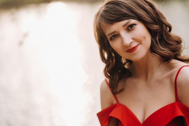 Portret młodej pięknej dziewczyny roześmianej z długimi brązowymi włosami, w długiej czerwonej sukience w przyrodzie, sezon to wiosna.
