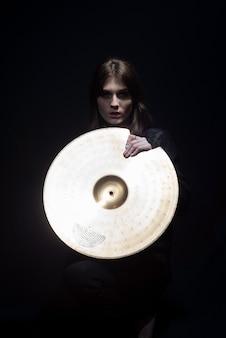 Portret młodej pięknej dziewczyny trzymającej błyszczący talerz bębna na czarnym tle
