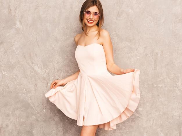 Portret młodej pięknej dziewczyny uśmiechający się w modne letnie światło różowa sukienka. seksowny beztroski kobiety pozować. pozytywny model zabawy