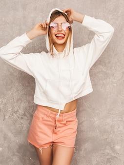 Portret młodej pięknej dziewczyny uśmiechający się w modne letnie ubrania sportowe. seksowny beztroski kobiety pozować. pozytywny model zabawy w okularach przeciwsłonecznych