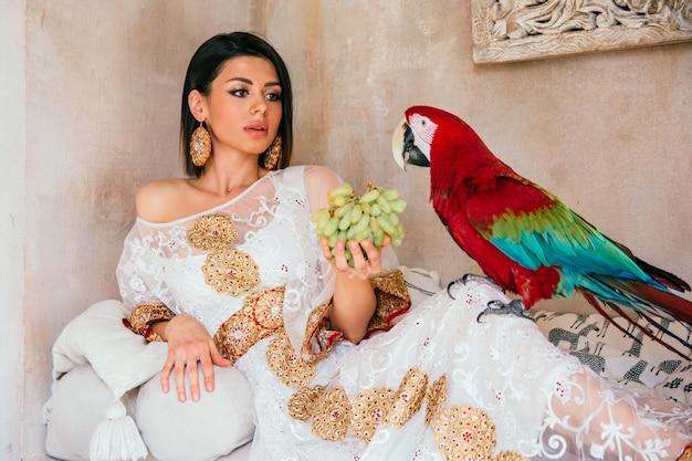 Portret młodej pięknej dziewczyny w białej sukni z papugą