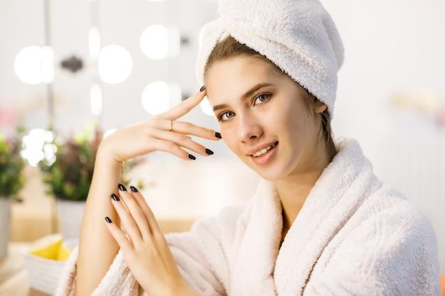 Portret młodej pięknej dziewczyny w białej szacie i ręczniku na głowie