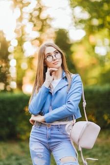 Portret młodej pięknej dziewczyny w okularach w dżinsach ze stylowymi spodniami