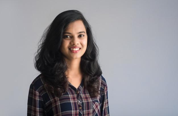 Portret młodej pięknej dziewczyny wesoły ładny uśmiechnięty na szarej ścianie