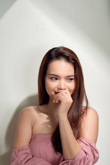 Portret młodej pięknej dziewczyny z długimi włosami, ubranej w różową bawełnianą bluzkę, stojącej nieśmiało chowającej się za ręką i uśmiechniętej, na białym tle