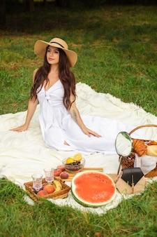 Portret młodej pięknej dziewczyny z równymi białymi zębami, pięknym uśmiechem w słomkowym kapeluszu i długiej białej sukni urządza piknik w ogrodzie