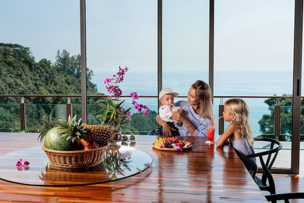 Portret młodej pięknej kaukaski rodziny matki i jej dwa słodkie małe dzieci, siedząc przy kuchennym stole w domu i jedząc razem śniadanie letnie wakacje