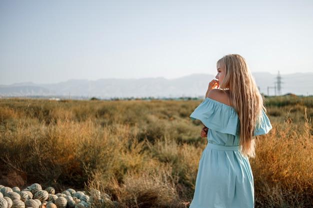 Portret młodej pięknej kaukaskiej blondynki dziewczyny w jasnoniebieskiej sukni stojącej na polu arbuza z suszoną trawą podczas zachodu słońca