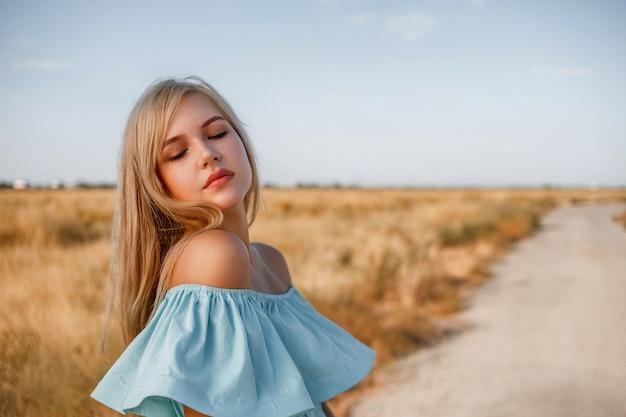 Portret młodej pięknej kaukaskiej blondynki dziewczyny w jasnoniebieskiej sukni stojącej na polu z suszoną trawą trawą obok małej wiejskiej drogi