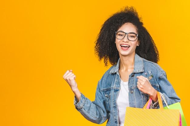Portret młodej pięknej kobiety afroamerykanów uśmiechnięta i radosna z kolorowych toreb na zakupy izolowanych na żółtym tle ściany pastelowe.