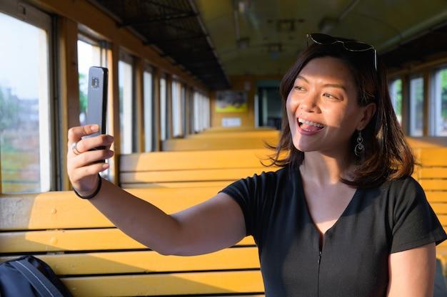 Portret młodej pięknej kobiety azjatyckich turystycznych jazdy pociągiem na stacji kolejowej hua lamphong