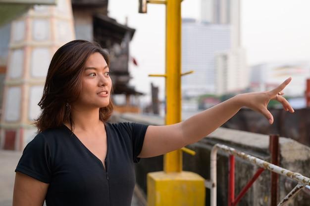 Portret młodej pięknej kobiety azjatyckich turystycznych na molo nad rzeką