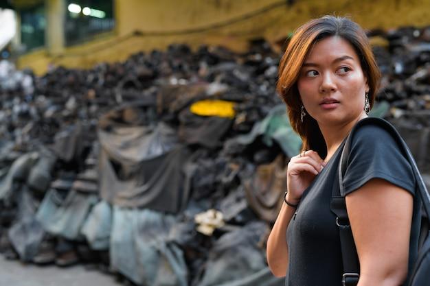 Portret młodej pięknej kobiety azjatyckich turystycznych w brudnych zaułkach bangkoku
